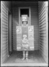 Outdoor portrait of an unidentified child in fancy dress as a 'Aulsebrook Biscuit' box, standing in the entrance of a house, possibly Christchurch district