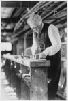 George Norton working at his bench in the Star Boating Club, Wellington