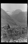 An unidentified man sitting next to a river, Lyell Glacier behind, Canterbury Region