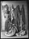 Maori carved figure wearing a piupiu and tiki, standing against a wall with weapons and cloaks.