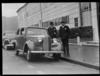 Two men standing beside parked Vauxhall 14 car
