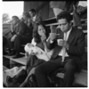 Opunake, young couple in grandstand; rugby game in sports grounds