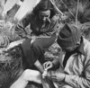 Bill Davidson performing first aid on Kath Boswell's foot during tramping expedition in Kaikoura Ranges