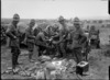 New Zealand machine gunners fitting machine gun belts with cartridges, France