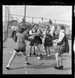 Men dressed in gym slips playing netball against women, Department of Health, Wellington
