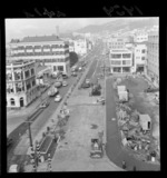 Taranaki Street, Wellington, looking toward Mount Cook, showing roadworks to widen the street, and buildings including JAS J Niven & Company Limited, and Wright Stephenson & Company Limited, with Dominion Museum in distance