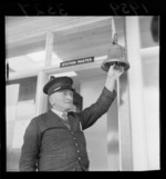 Mr Linklater, Stationmaster, ringing a train bell at Porirua, Wellington