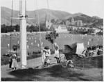 Children playing beside a pram, Basin Reserve, Wellington