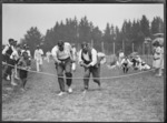 Men competing in an egg and spoon race