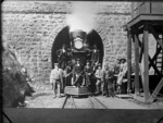 Steam locomotive at the mouth of the Lyttelton Tunnel, with a group of men standing on and in front of the engine