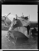 Tasman Empire Airways Limited crew watch on as the Short S.45 Solent flying boat, R.M.A Araragi (ZK-AMM), is moored by a man leaning out of the nose of the aircraft, Evans Bay, Wellington