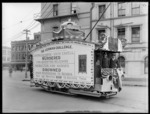 Tram decorated with World War 1 propaganda, including unidentified tram conductor and passenger, Temperance and General Life Assurance Society building in background, Cathedral Square, Christchurch