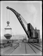 View of the wharf area, Westport, with crane on rails lifting coal bucket to load coal wagons with man looking on, commercial buildings and other crane operating beside the wharf background, Westport Harbour