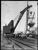 Wharf area, Westport, with crane on rails lifting coal bucket, ship and Westport Harbour beyond