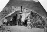 Two Chinese miners with Reverend George McNeur outside a stone house near Arrow Falls