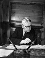 Walter Nash sitting at his desk in the legation chancery, Washington