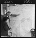 Unidentifiefd man and woman, surveying a map of stock control and infected areas, conference on diseases in the Wairarapa district, Wellington