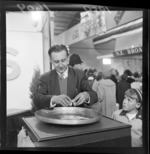 Unidentified man cracking open an egg while a little boy looks on at the Wellington Industries Fair exhibits
