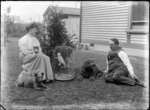 Unidentified man and woman, with domestic pets outside a house, shows a cat, dogs and a parrot, probably Christchurch district