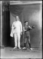 Studio portrait of unidentified man and boy, one wearing a boxing outfit with shorts, boots and boxing gloves, the other wearing a jersey and pants and  holding a towel, most likely boxer and coach, Christchurch