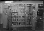 Interior view of the Transmission House, Musick Point Air Radio Station, Howick, Auckland, showing two unidentified men checking transmission cabinets