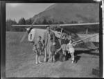 Portrait of Mr E F Harvie with his four children in a field in front of Auster J-1B Autocrat ZK-AOB plane, Queenstown, Otago Region