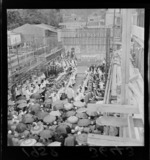 Service in the roofless Anglican Cathedral, Wellington, under construction, with altar, choir and umbrellas