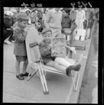 Spectators at a Wellington parade, including two unidentified small boys in school uniform, one with a broken leg in a plaster cast, who is sitting in a folding chair and reading Jack and Jill childrens' magazine
