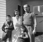 Man and woman, with two children, in front of a house