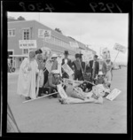 Parade at Wainuiomata, Wellington, for swimming baths fund, showing unidentified young men dressed in costumes and holding signs