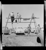 Men sitting on a make-shift scaffolding, watching race, at the New Zealand Grand Prix, Ardmore Airport, Manukau, Auckland
