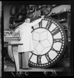 A large clock from a town clock tower being dismantled by an unidentified man, Petone, Lower Hutt, Wellingtonl Region
