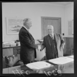 Sir Walter Nash (Prime Minister) shaking hands with American Ambassador Mr F H Russell, after signing an agreement