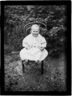 Edgar Williams as a baby sitting on a chair holding flowers in the garden of their home 'View Bank', Maitland Street, Dunedin