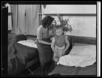 003669: An unidentified woman helping a young boy to get dressed, at Polish children's refugee camp, Pahiatua