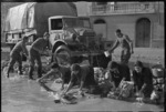 New Zealand soldiers cleaning a truck, and local Italian women washing their linen, near Alife, Italy, during World War 2