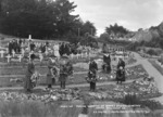Group placing wreaths on graves in the soldiers section of the Karori Cemetery, Karori, Wellington, on Anzac Day, 1921