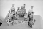 Display of household consumer items, mainly food, with prices attached, showing rising costs between 1972 and 1975
