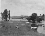 Woman sitting beside Lake Taupo at the mouth of the Waikato River
