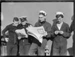 Sailors from HMS Leander, reading newspapers