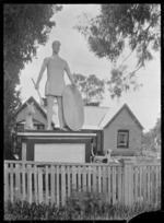 "Front view of ""Rose Cottage"", Moroa, near Greytown, with a statue of an ancient warrior standing on a pedestal in front of the house."