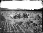 Men and horses in a harvested oat field, on the farm Marathon, near Seddon, Marlborough - Photograph taken by Arthur John  McCusker