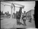 Soldier standing beside his horse.