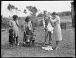 District nurse weighing a baby, Northland