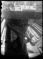 View of the stern of a ship showing the propellers with men working at the bottom of an unidentified dry dock