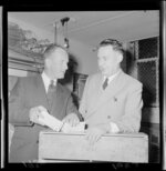 Two unidentified men demonstrating how the new egg cartons can be divided in half