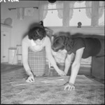 Mrs Holmes and a neighbour cutting a pattern, 32 Naenae Road, Hutt Valley