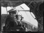 Captain looking through a sextant [?] in the seaplane Aotearoa in Suva, Fiji survey flight