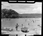 Unidentified child playing in the sand with a man watching while others swimm and boat, Whitianga harbour