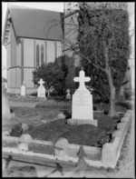 Exterior view of a unidentified wooden Anglican church and graveyard, Papanui, Christchurch, with grave of George and Louisa Dunnage in foreground